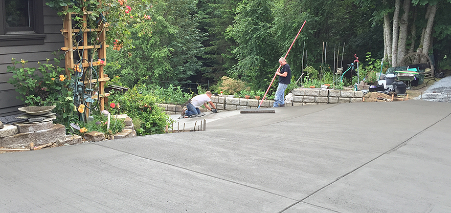 Artistic Concrete installing a new slate Integral colored concrete driveway with a fine tbroom finish in the Camano Island area.